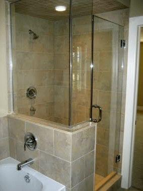 Glass wall shower with bathtub beside it in a bathroom