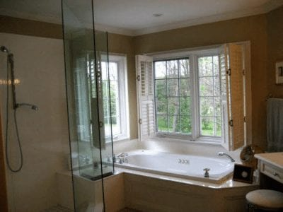 Large glass wall shower with bathtub beside it in a bathroom