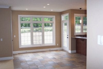 Dining area leading into a kitchen and a door to the backyard