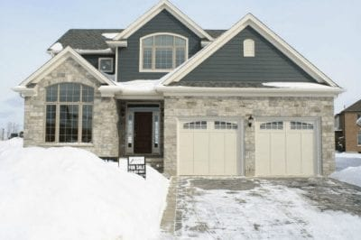 Two-storey brick house with an interlock driveway, snowed in