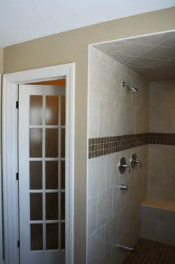 A large walk-in shower with stone bench and a door leading out of the shower room