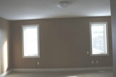 An empty room with two vertical windows