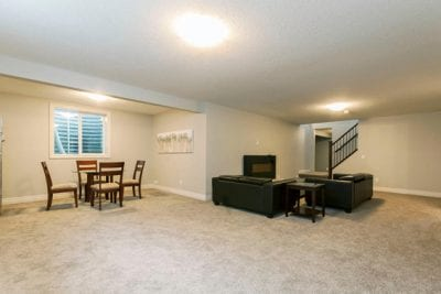 A large room with sparse furnishing including a small table, some chairs and some couches