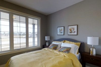 Small bedroom with glass pane window overlooking the front yard