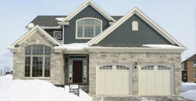 Two-storey brick house with an interlock driveway. snowed in